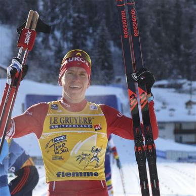 First placed Russia's Alexander Bolshunov poses for photo at the finish area of a Tour de Ski, men's 15-kilometer mass start classic cross-country ski event in Val di Fiemme, Italy, Friday, Jan. 8, 2021 (AP Photo/Alessandro Trovati)