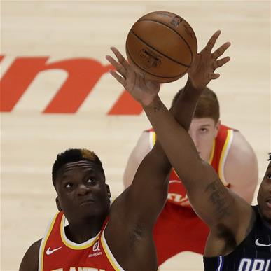 Atlanta Hawks' Clint Capela (15) and Orlando Magic center Wendell Carter Jr., right, fight for the opening tip off during the first half of an NBA basketball game Tuesday, April 20, 2021, in Atlanta. (AP Photo/Ben Margot)